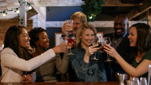 blonde woman enjoying festive drinks with friends in bar